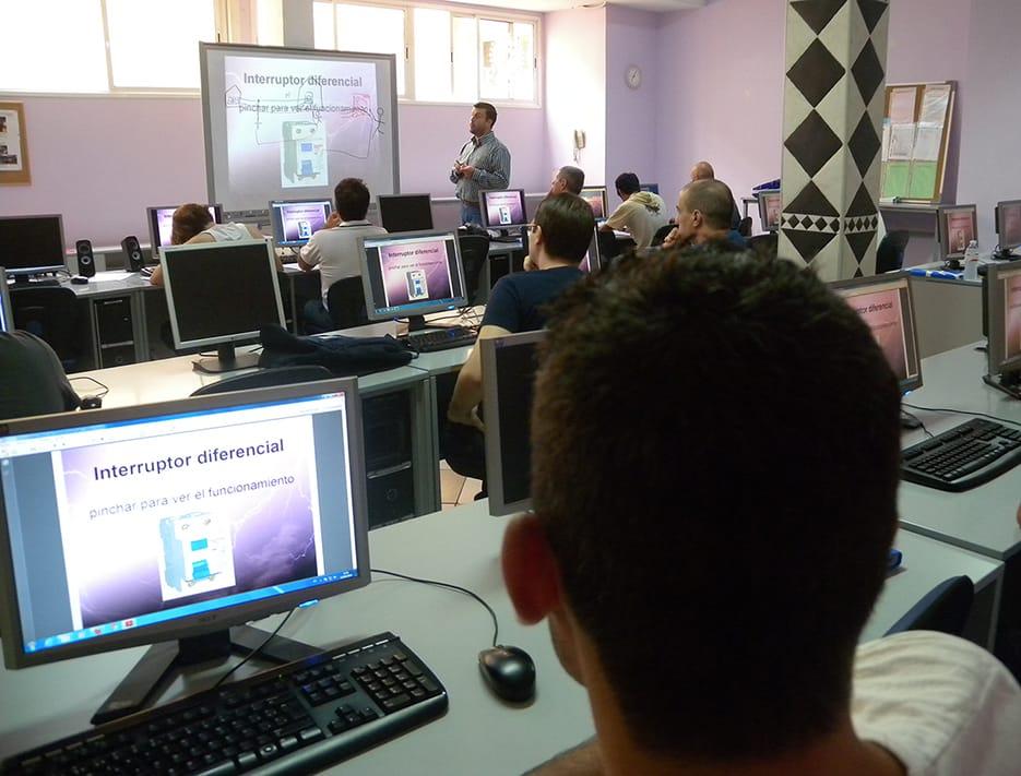 Vista general de un aula informática con los alumnos y el profesor en la pizarra digital