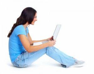 Chica morena sentada en el suelo de perfil con un portátil en sus rodillas en fondo blanco.Accede a la plataforma online de Focan
