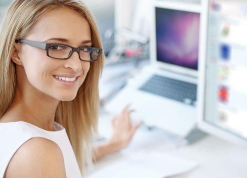 Mujer rubia con gafas de pasta sonriendo hacia la cámara trabajando en dos ordenadores