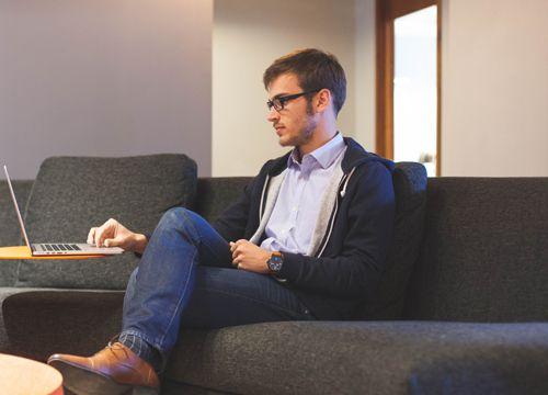 chico con gafas sentado relajado en una sala de reuniones consultando algo en un portátil