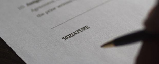 Primer plano de un bolígrafo y un papel en el acto de firmar un convenio