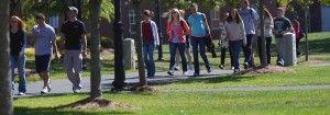 Jóvenes en un campus universitario con césped