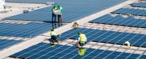 Vista aérea de un huerto solar en lo alto de un edificio y técnicos trabajando