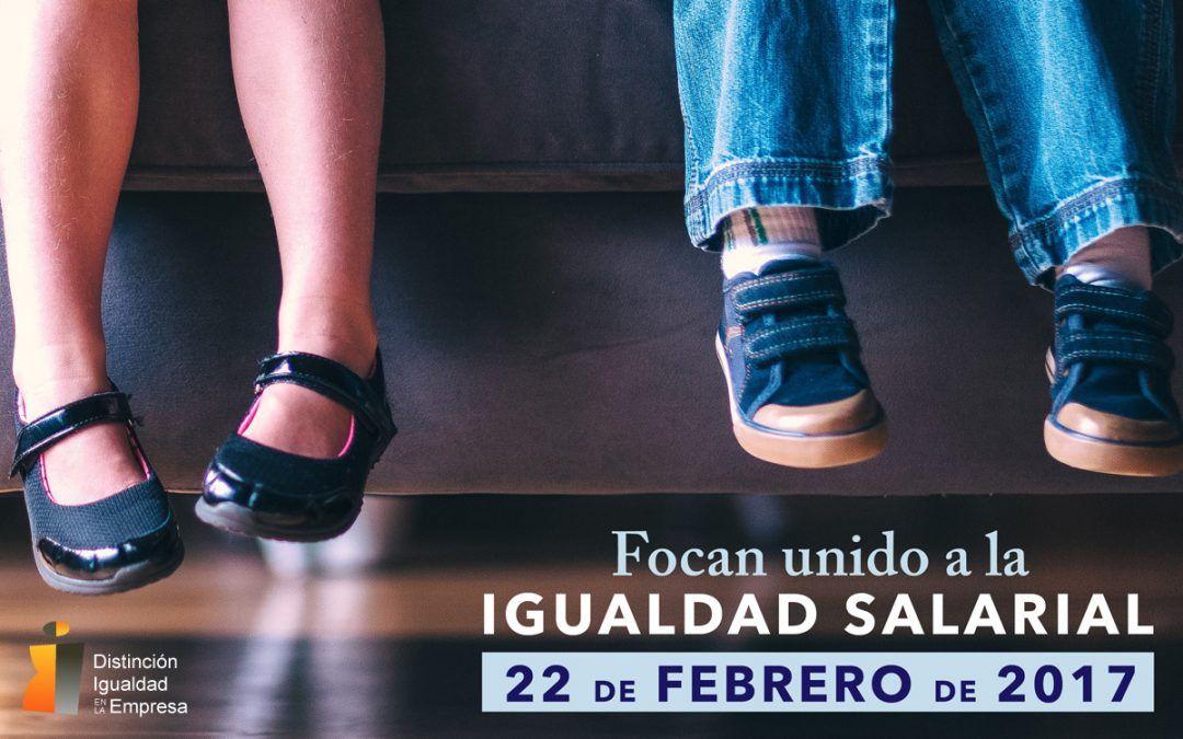 Primer plano de unos pies colgando de un niño y una niña en un sofá oscuro, con motivo del día internacional de la igualdad salarial