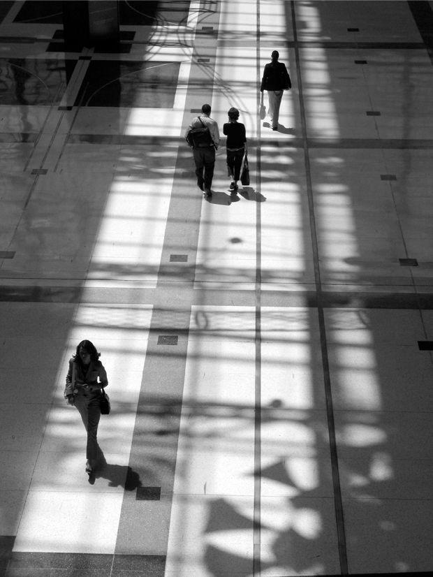 Foto en blanco y negro de varias personas caminando en un andén con fuerte contraluz y contraste