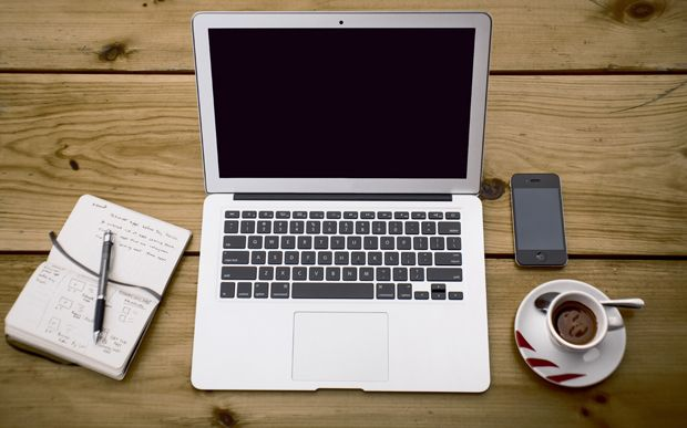 Vista cenital de un portátil, un cuaderno de notas, un móvil y un café sobre una mesa de madera