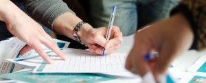 Primer plano de la mano de una mujer rellenando un formulario en una mesa llena de papeles