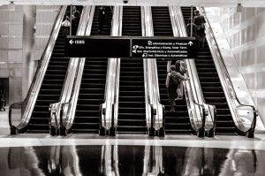 Plano general de unas escaleras mecánica con personas y un cartel luminoso que indica los ciclos de ISBS
